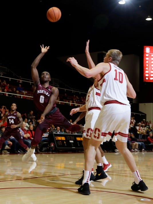 Montana guard Michael Oguine (0) shoots over Stanford forward Michael Humphrey (10) and another defender during the first half of an NCAA college basketball game Wednesday, Nov. 29, 2017, in Stanford, Calif. (AP Photo/Marcio Jose Sanchez)