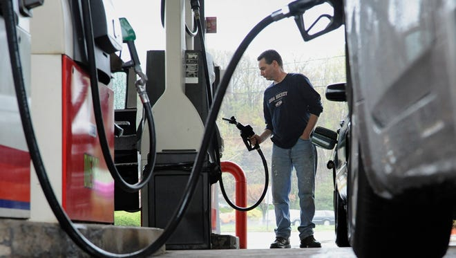A man pumps gas at a station in Wethersfield, Conn.