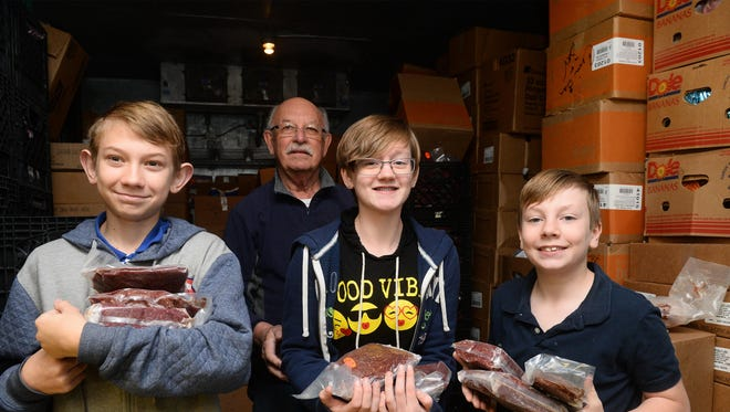 Chris Christiaens, a St. Vincent de Paul volunteer, stands with student volunteers from Five Falls Christian School who are holding some of the 550 pounds of game meat that has been donated to the food pantry. The students are, from left, Jerimiah Denio, Reighanna Miller and J.D. Miller.