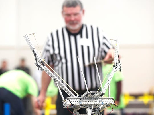 A referee watches a robot on the competition floor