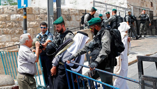 Palestinian Muslim worshippers speak with Israeli border guards outside the Lions Gate, a main entrance to Al-Aqsa mosque compound, in Jerusalem's Old City on July 21, 2017, after Israel barred men under 50 from entering the Old City for Friday prayers.