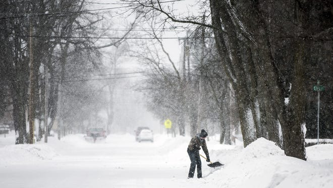 A man shovels snow on Main Street in Stevens Point, Wis., during a spring blizzard on Sunday, April 15, 2018.