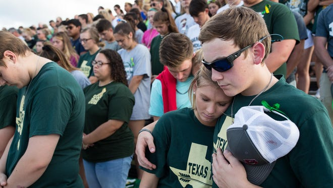 Santa Fe students bow their heads during a moment of silence before a baseball playoff game against Kingwood Park to honor the 10 who died in Friday's shooting.