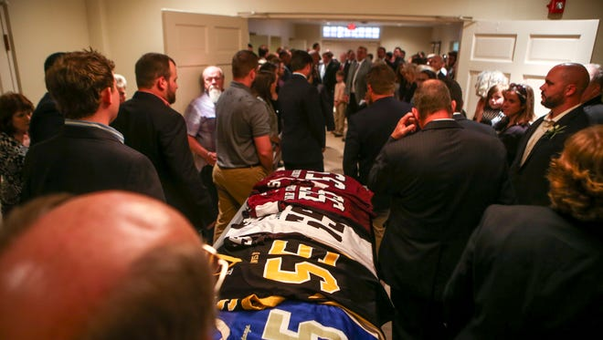 Pallbearers wait alongside the casket of Will Fisher, decorated in jerseys from schools he played or coached at at the celebration of life service for William Keith Fisher at First United Methodist Church in Huntingdon, Tenn., on Thursday, Sept. 6, 2018.