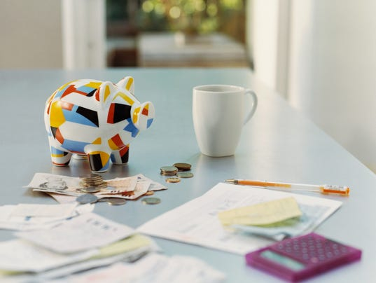 Piggybank, British Currency, Calculator, Receipts and a Mug on a Table