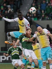 Columbus Crew forward Kei Kamara, left, Portland Timbers defender Nat Borchers, center and Columbus Crew forward Conor Casey (27) battle for the ball during the second half of an MLS soccer match in Portland, Ore., Sunday, March 6, 2016. The Portland Timbers won 2-1.