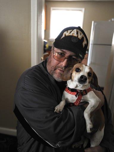 Navy vet Ben Elliott, 46, hugs his dog Cookie at home