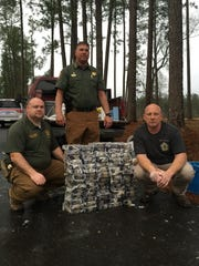 Sheriff Jody Ashley, standing, and two of his investigators with the more than 70 kilos of cocaine confiscated in March 2016.