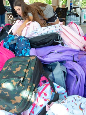 Lilianna Ortiz, 13, of Las Cruces, reaches for a backpack to give away during FYI's second annual back-to-school event at Pioneer Park. Ortiz was able to donate 135 backpacks towards the event, all on her own.