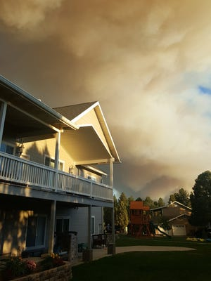 Smoke from the Cedar Creek Fire looms near a home in Show Low on June 15, 2016.