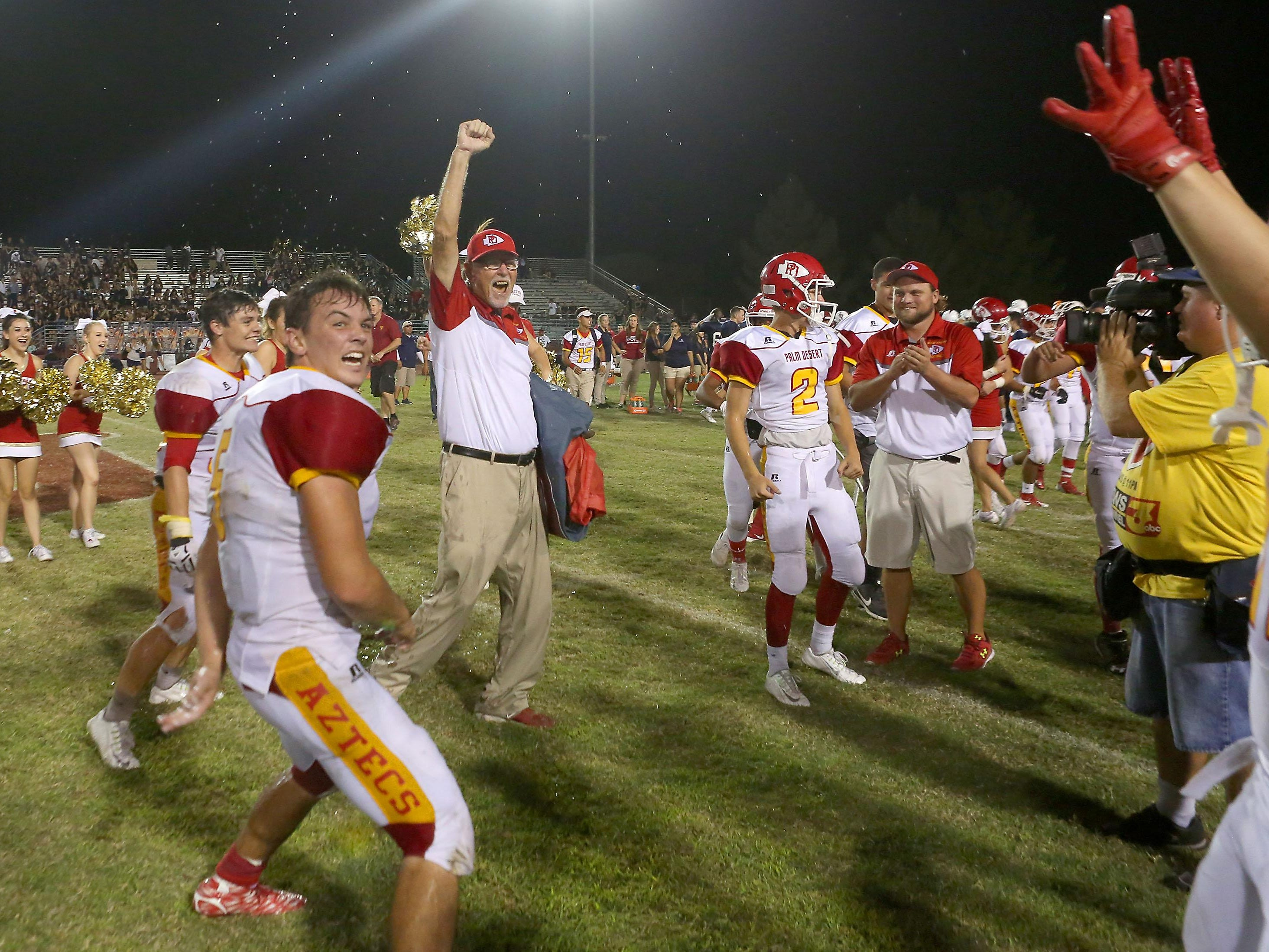 Palm Desert coach Pat Blackburn celebrates the return of the flag after beating La Quinta, Friday, September 25, 2015.