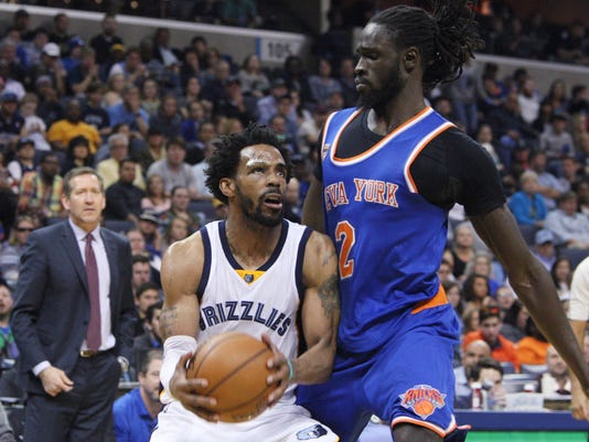 Memphis Grizzlies' Mike Conley (11) starts to shoot as New York Knicks' Maurice Ndour (2) defends during the second half of an NBA basketball game Friday, April 7, 2017, in Memphis, Tenn. (AP Photo/Karen Pulfer Focht)