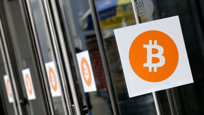 Bitcoin logos are displayed at the Inside Bitcoins conference and trade show in New York. A federal regulator gave the go ahead on Friday, Dec. 1, 2017,  to the CME Group to start trading bitcoin futures later this month, the first time the digital currency will be traded on a Wall Street exchange and subject to federal oversight.