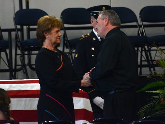 The Rev. Craig Scott (right) visits with Sara Strother, mother of the late National Guardsman David Strother, during visitation Wednesday in the Alexandria Riverfront Center.