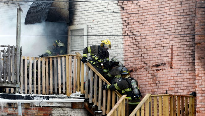 Toledo firefighters rush a fellow firefighter down the stairs of a six unit apartment building in Toledo, Ohio on Sunday.