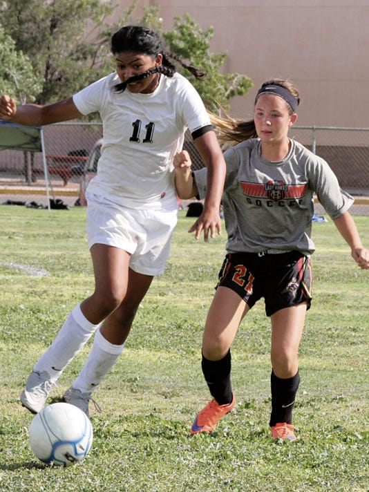 "Bill Armendariz - Headlight Photo   Lady Cat Alyssa ""Cheeks"" Magana (11) works to get a free ball past a Centennial High midfielder during Saturday's round-robin scrimmage session at the Deming High Soccer Field."