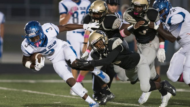 Dana Brown of Barron Collier is tackled by Anthony Robinson of Golden Gate (5) during the game at Golden Gate High School Friday night, October 14, 2016.