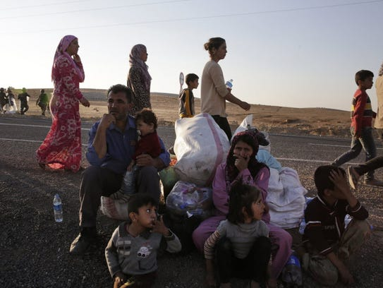 Kurdish refugees wait by the side of the road near
