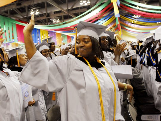 FILE PHOTO : Shaquila West waves to her family in recognition of their help in her graduation at the Southern University at Shreveport Commencement Ceremony.