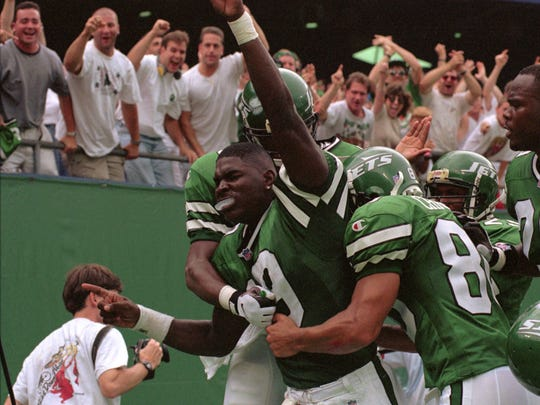 Jets' Keyshawn Johnson (19) getting hugged by teammates after scoring a touchdown against the Indianapolis Colts in 1996 at Giants Stadium.