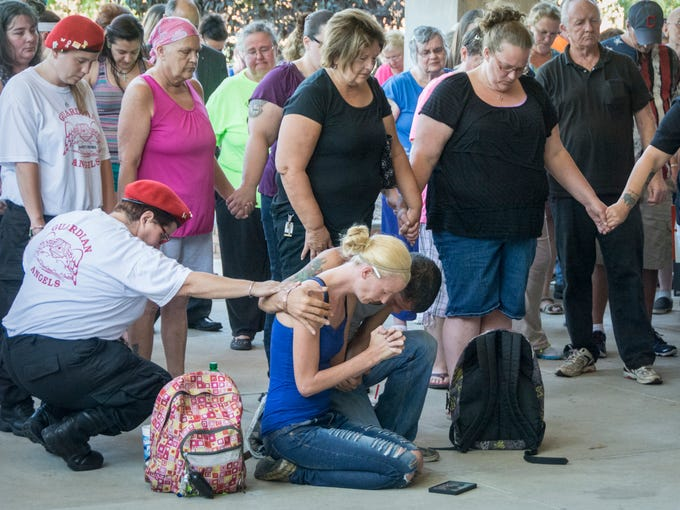 Sarah Lewis is comforted by Danny Noggle III and a member of the Bucyrus Guardian Angels as prayers are said. Family members, friends and officials gathered on the steps of the Bucyrus City Hall to remember the four men who were killed in the city during the Labor Day Weekend.