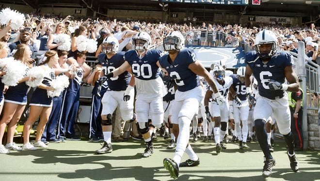 Penn State football players enter the field for the first half of Penn State's spring football scrimmage, the Blue-White Game, Saturday in State College. The blue squad won, 37-0.