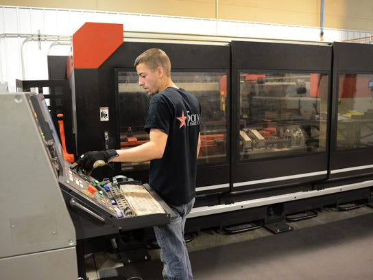 Lee Athey works on the laser cutting machine at 5