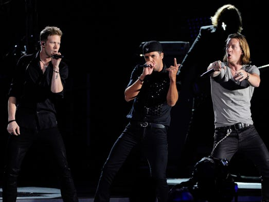 Luke Bryan, center, performs with Florida Georgia Line at the 47th annual CMA Awards at the Bridgestone Arena in Nashville on Nov. 6.