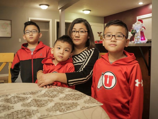 Ester Kiim of Des Moines holds her youngest son, Martin Suum, 5, at the kitchen table of their new home in Clive on Tuesday, Dec. 19, 2017, as her other two sons Suan Mung, left, and David Tuang, stand at her side. Kim was left a widow after her husband was shot to death after an attempted robbery in April, 2017.