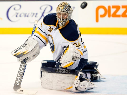 Buffalo Sabres goaltender Michal Neuvirth watches the puck after making a save against the Toronto Maple Leafs during the second period of an NHL hockey game, Tuesday, Oct. 28, 2014 in Toronto. (AP Photo/The Canadian Press, Frank Gunn)