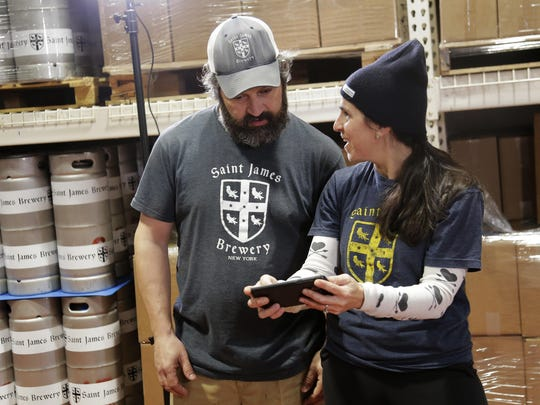 In this March 4, 2019, photo, Jamie Adams and his wife Rachel Adams look at an image of a banner for their new beer, Deep Ascent, at their St. James Brewery in Holbrook, N.Y.