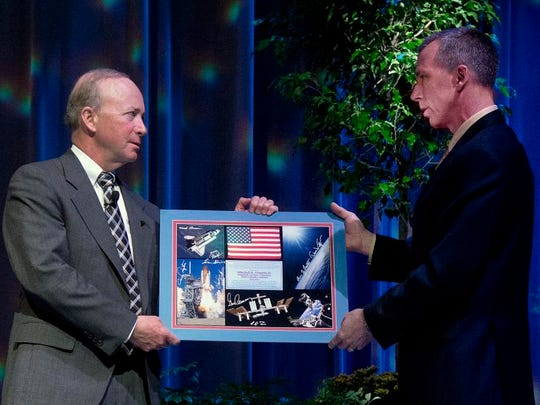 Andrew Feustel gives Purdue President Mitch Daniels a collage of photos signed by other Purdue-produced astronauts during a forum Saturday at Elliott Hall of Music.