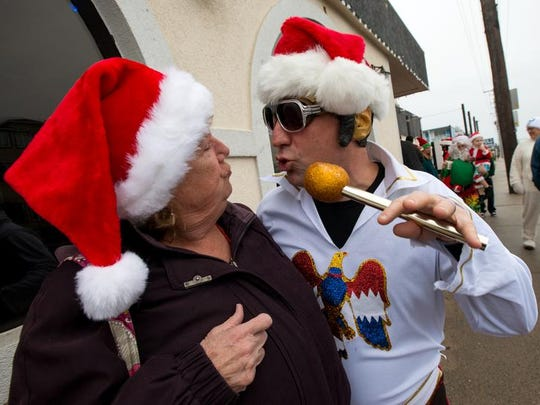 Mariana Mieman of Ocean Pines, left, is serenaded by Joe Travaglini, aka Elvis Santa, in front of the Pit and Pub during SantaCon in Ocean City Saturday afternoon.