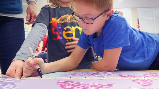 First graders Clara Catlin and Charlie Bohmann mark tape on fleece cloth to be cut and tied into a blanket during Wilson Elementary/Wilson STEM's Service Day with five different projects to benefit local  groups and American servicemen on Nov. 21.