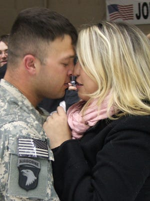 Spc. Jonathan Word kisses his wife Courtney after returning to Fort Campbell from his first deployment in October 2008.