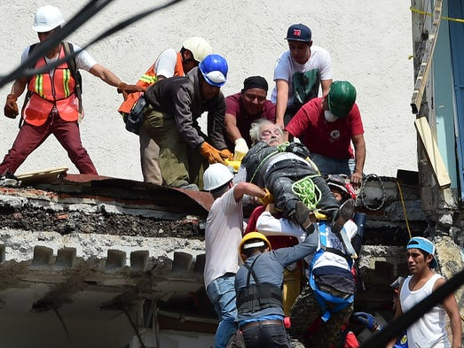 A man is pulled out of the rubble alive following a