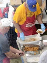 File - Food is prepared at a previous Rogers Street Days event at the Rogers Street Fishing Village and Great Lakes Coast Guard Museum in Two Rivers.