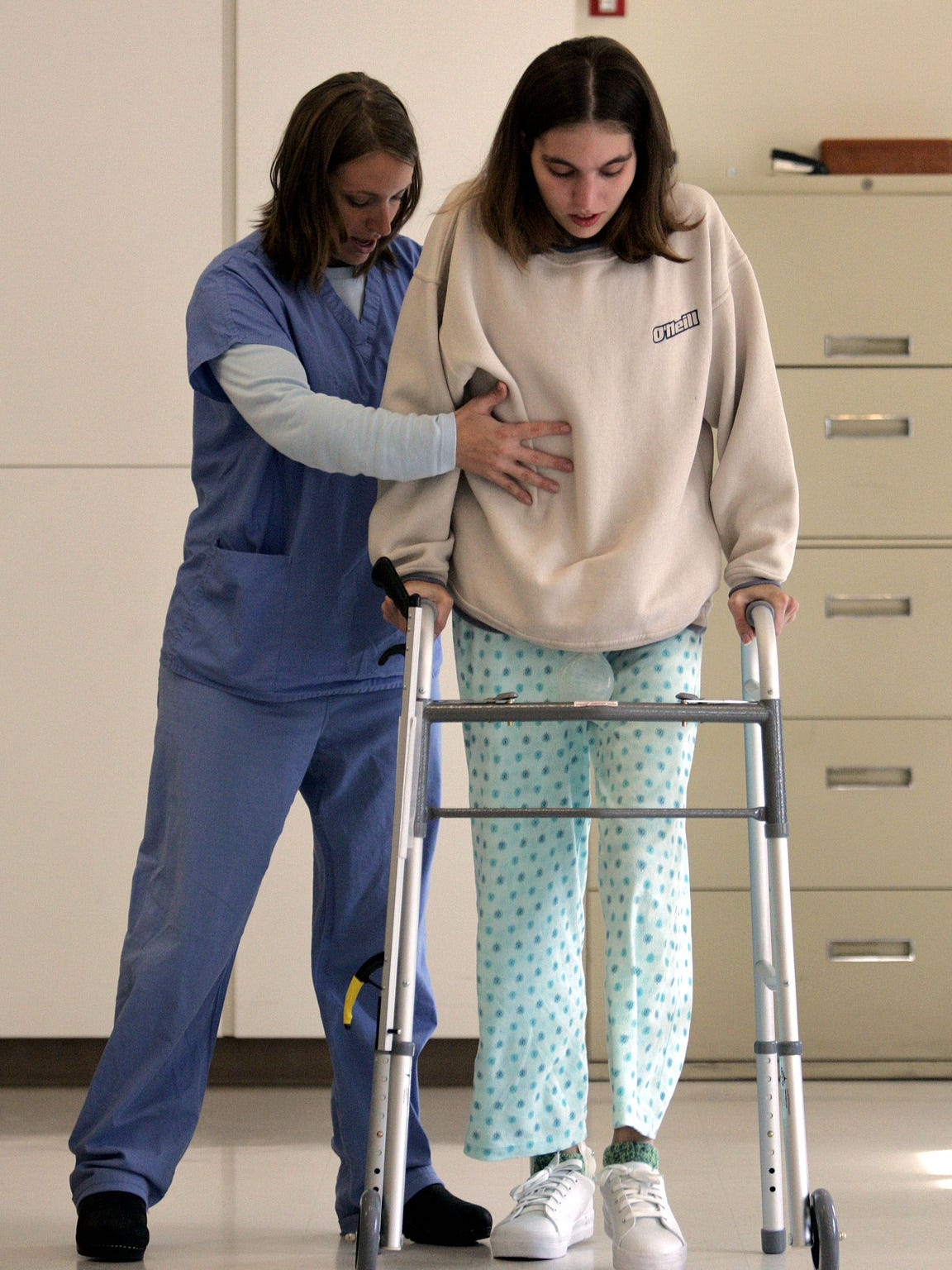 Occupational therapist Amy Cisler, left, reaches out