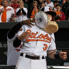Sep 15, 2014; Baltimore, MD, USA; Baltimore Orioles center fielder Adam Jones (10) pies  third baseman Ryan Flaherty (3) during a post game interview after defeating the Toronto Blue Jays 5-2 at Oriole Park at Camden Yards. Mandatory Credit: Tommy Gilligan-USA TODAY Sports