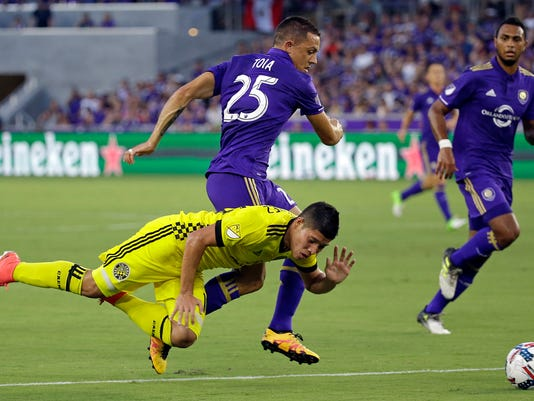 Columbus Crew's Cristian Martinez, front left, falls after becoming entangled with Orlando City's Donny Toia (25) during the first half of an MLS soccer match, Saturday, Aug. 19, 2017, in Orlando, Fla. (AP Photo/John Raoux)