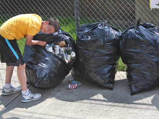 Alex Walters, with the Mooresville High School soccer team, laughs as a full bag of trash rips and starts to spill during a day of clean up at the Indianapolis Motor Speedway, Monday, May 26, 2014, the day after the Indy 500.  Many groups, like the soccer team, clean up at the track as a fundraiser.