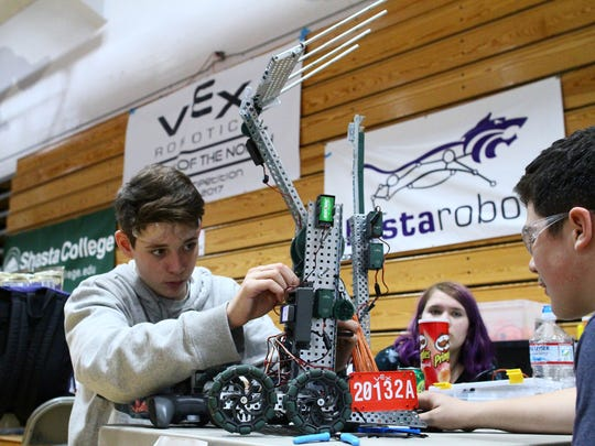 Tyce Kelley, left, of Central Valley High School works on his team's robot at Saturday's competition while teammates Katy Woodmansee, center, and Logan Ross look on.