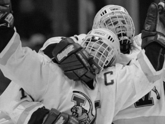 Vermont's Martin St. Louis, left, celebrates with teammates