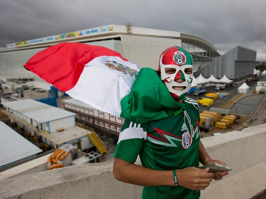 Backdropped by the Itaquerao stadium, a Mexico soccer fan poses for a photo wearing a wrestling mask and a representation of his country's national flag as a cape, in Sao Paulo, Brazil, Tuesday, June 10, 2014. The high-profile inaugural match will be played at the troubled Itaquerao, which was one of the most delayed venues for the World Cup. It's already known that the stadium's roof won't be fully finished until after the tournament. (AP Photo/Eduardo Verdugo)