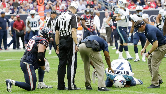 Houston Texans' J.J. Watt (99) watches as Tennessee Titans' Zach Mettenberger is attended to after being hurt during the second half of an NFL football game Sunday, Nov. 30, 2014, in Houston. (AP Photo/David J. Phillip)