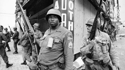 In this July 14, 1967, file photo, National Guardsmen stand at the corner of Springfield Avenue and Mercer Street in Newark, where days of violence and looting came to be known as the Newark riots.