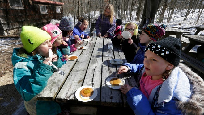 Girl Scouts and 4-H groups enjoy a warm pancake and pickle with maple syrup during a visit to the sugar bush at Riveredge Nature Center in Saukville.