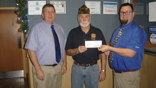 VFW Post 2534 Commander Tom Sachs, center, receives a check from Culver's Family Restaurant co-owners Greg Giese, left, and Brad Prohl.