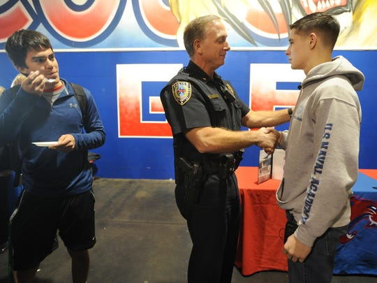 Assistant Police Chief Mike Perry, center, congratulates Michael Shubert, right, on his acceptance in the United States Naval Academy.