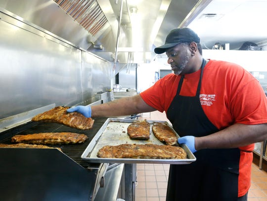 Assistant manager Patrick Schuyler places ribs on the